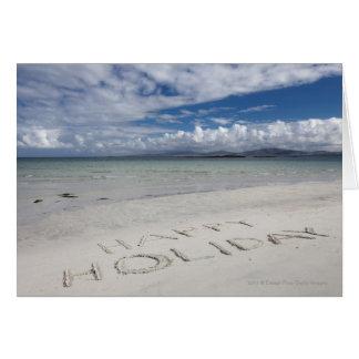 Tarjeta Día de fiesta feliz escrito en la playa de