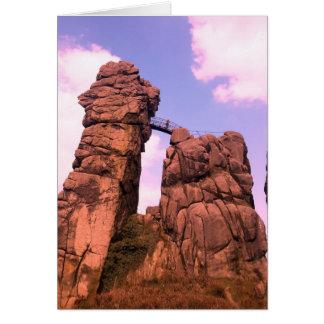 Tarjeta dos rocas grandes y puente de madera en parque de