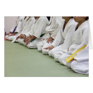 Tarjeta El jugador del judo del niño se sienta a una línea