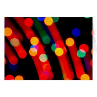 Tarjeta Las luces de navidad de Bokeh con la luz arrastran