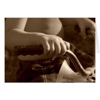 Tarjeta manos del niño en el triciclo