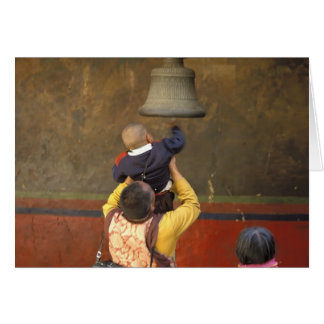 Tarjeta Monje budista tibetano que levanta a un muchacho