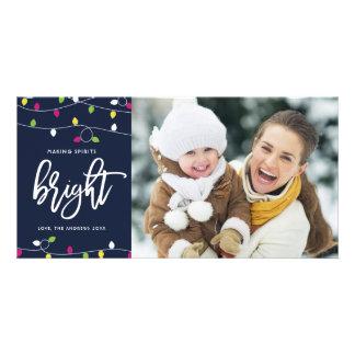 Tarjeta Navidad brillante y colorido de las luces de