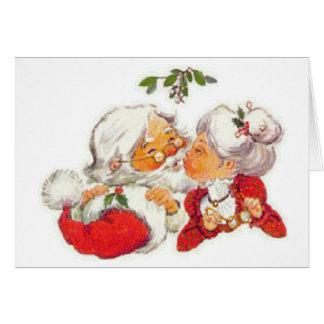 Tarjeta Navidad Santa del vintage que besa a señora Claus
