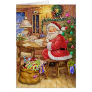 Tarjeta Papá Noel que trabaja en su escritorio