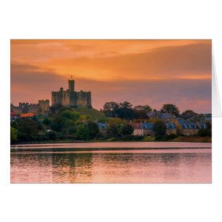 Tarjeta Pueblo y castillo de Warkworth en la puesta del