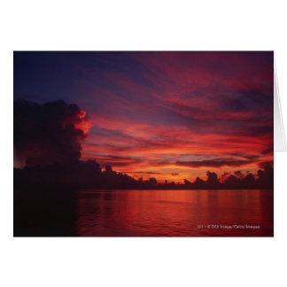 Tarjeta Puesta del sol en el mar con las nubes oscuras