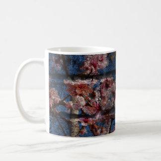 Taza azul del ladrillo y de los flores