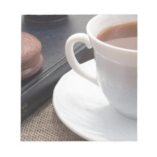Taza blanca de cacao caliente y de una galleta del bloc de notas