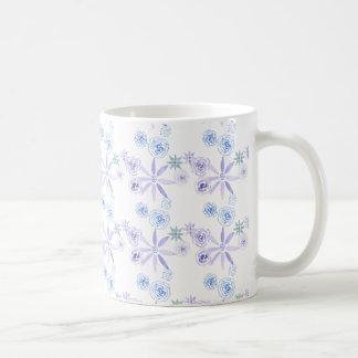 Taza con las flores azules y púrpuras de la