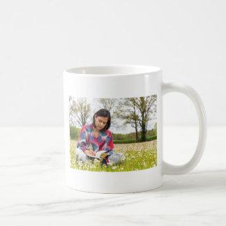 Taza De Café Escritura de la mujer en prado con las flores de
