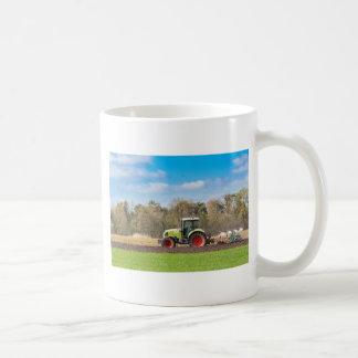 Taza De Café Granjero en el tractor que ara el suelo arenoso en