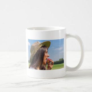 Taza De Café Mujer con el gorra que come la manzana roja afuera