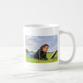 Taza De Café Mujer joven que miente en libro de lectura de la