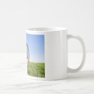Taza De Café Mujer que se arrodilla en la hierba que mira