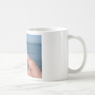 Taza De Café Sostener un seashell en la mano con el mar azul