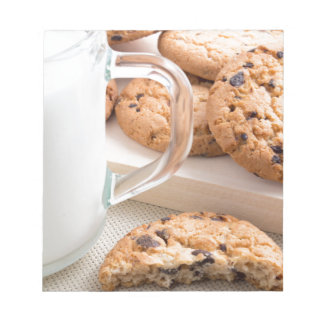 Taza de cristal con las galletas de la leche y de bloc de notas
