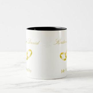 Taza del boda con los anillos de oro unidos