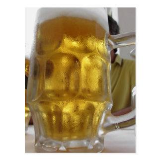 Taza fría de cerveza ligera en la tabla en un postal
