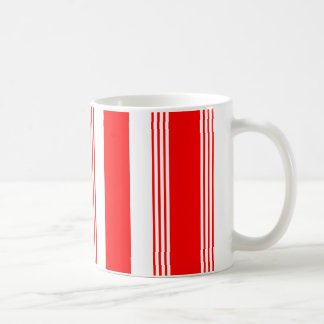 Taza rayada del caramelo mostrada en rojo cardinal