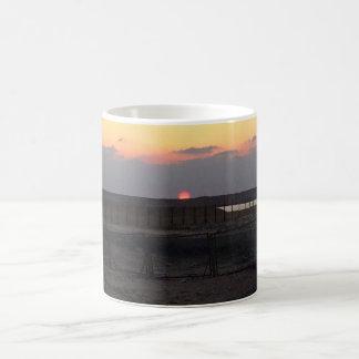 tazas del café y del viaje de la puesta del sol