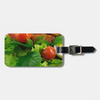 Tomates de cereza, hierbas, aceite de oliva, etiqueta para maletas
