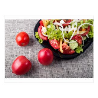 Tomates frescos y una pieza de una placa postal