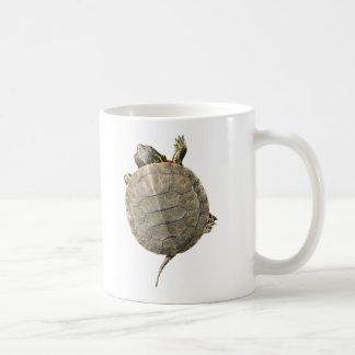 Tortuga minúscula que se arrastra encima del lado taza de café