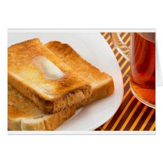 Tostada caliente con mantequilla en una placa tarjeta