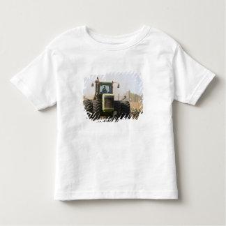 Tractor grande que cultiva el suelo de la camiseta