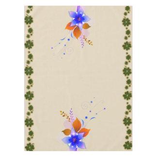 Trébol irlandés y mantel azul de las flores del