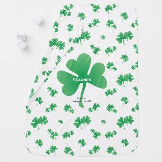 Tréboles irlandeses verdes de la pendiente con el mantita para bebé