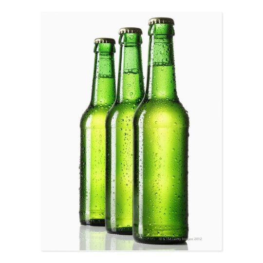 Tres botellas verdes de cerveza en el fondo postal