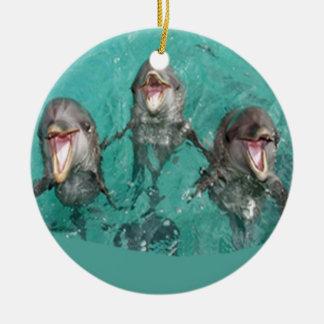 Tres delfínes en el océano adorno navideño redondo de cerámica