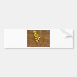 Tres lápices usados en la tabla de madera pegatina para coche