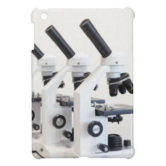 Tres microscopios en una fila aislada en fondo