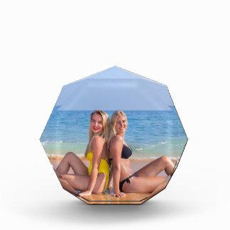 Trofeo Acrílico Dos chicas se sientan en la playa cerca de sea.JPG