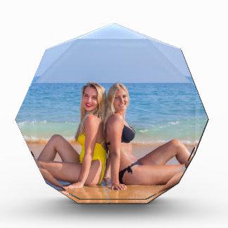 Trofeo Dos chicas se sientan en la playa cerca de sea.JPG