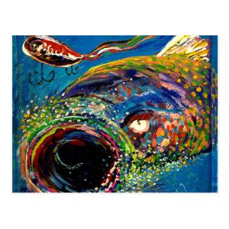 Trucha arco iris que sigue un señuelo de la pesca postal