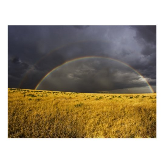 Un arco iris que aparece con un brumoso después de postal
