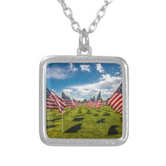Un campo de banderas americanas en la collar plateado