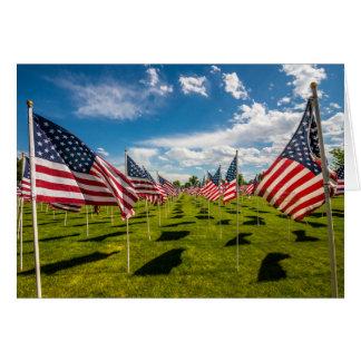 Un campo de banderas americanas en la tarjeta de felicitación