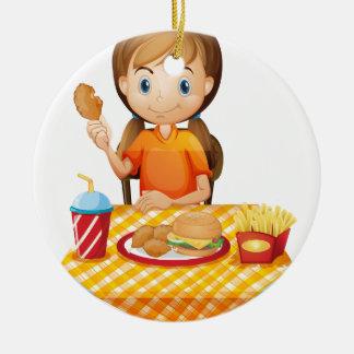 Un chica bonito que come en el restaurante de ornamentos de reyes magos