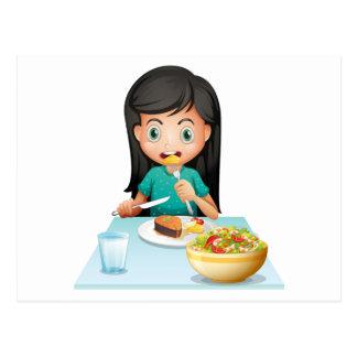 Un chica que come su almuerzo postal