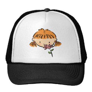 Un chica que huele una flor rosada gorra