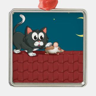 Un gato y un ratón en el tejado adorno navideño cuadrado de metal