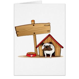 Un letrero al lado de una caseta de perro con un tarjeta de felicitación