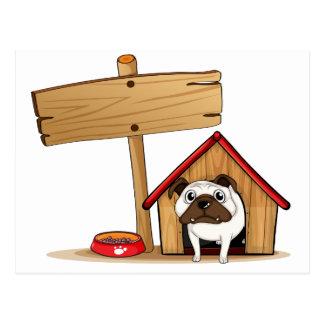 Un letrero al lado de una caseta de perro con un postal