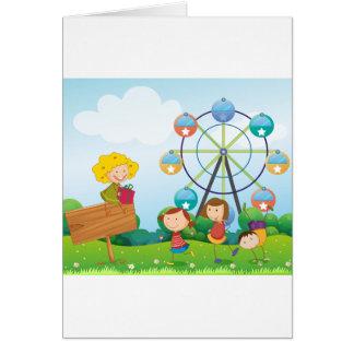 Un letrero vacío con los niños acerca a una noria tarjeta de felicitación