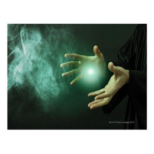 Un mago de la fantasía que hace magia con sus mano tarjetas postales